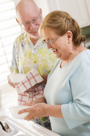 Senior Adult Couple Having Fun Washing Dishes Together Inside Kitchen of Their House. photo