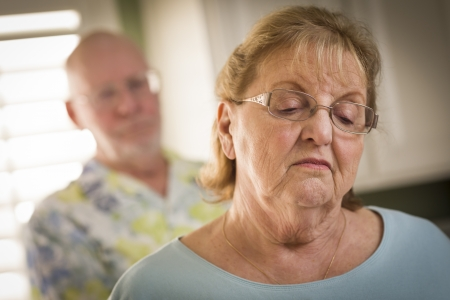 solace: Senior Adult Couple in Dispute or Consoling in Kitchen of House. Stock Photo