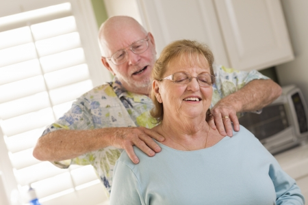 back rub: Happy Senior Adult Husband Giving Wife a Shoulder Rub in the Kitchen. Stock Photo