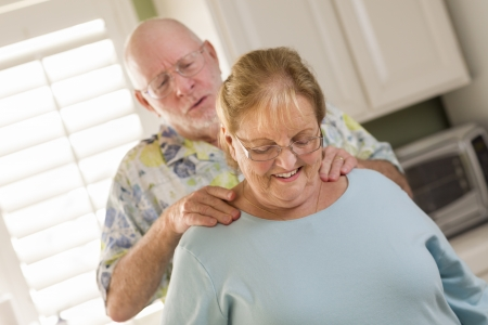Happy Senior Adult Husband Giving Wife a Shoulder Rub in the Kitchen. photo