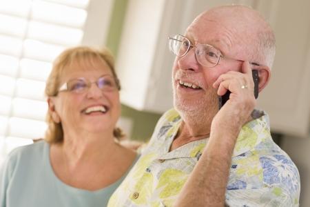 llamando: Mayor feliz esposo adulto en el teléfono celular con la esposa detrás en la cocina. Foto de archivo