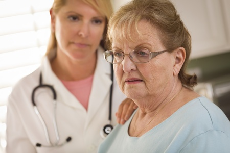 senior depression: Melancholy Senior Adult Woman Being Consoled by Female Doctor or Nurse. Stock Photo