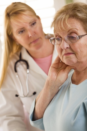 solace: Melancholy Senior Adult Woman Being Consoled by Female Doctor or Nurse. Stock Photo