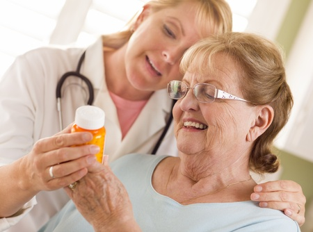 clarifying: Happy Female Doctor or Nurse Explaining Prescription to Senior Adult Woman.