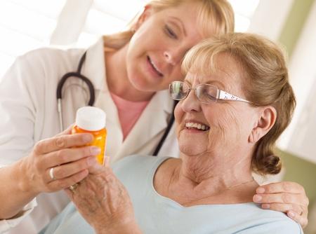 clarifying: Happy Female Doctor or Nurse Explaining Prescription to Senior Adult Woman.