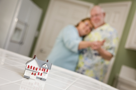 real estate planning: Happy Senior Adult Couple Dancing Together and Gazing Over Small Model Home on Their Kitchen Counter. Stock Photo