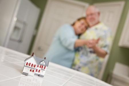 planificación familiar: Pares adultos mayores felices bailando juntos y mirando sobre la pequeña casa modelo en su cocina.