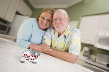 Happy Senior Adult Couple Gazing Over Small Model Home on Their Kitchen Counter. photo