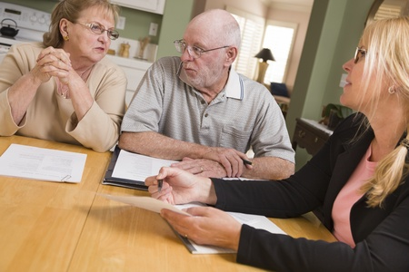 real estate planning: Senior Adult Couple Going Over Papers in Their Home with Agent.