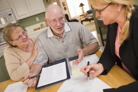 Realtor: Senior Adult Couple Going Over Papers in Their Home with Agent.