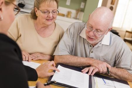 planeaci�n: Pareja Tercera edad Going Over trabajos en su casa con un agente. Foto de archivo