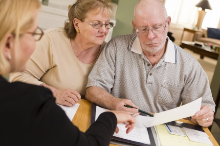 refinance: Senior Adult Couple Going Over Papers in Their Home with Agent.