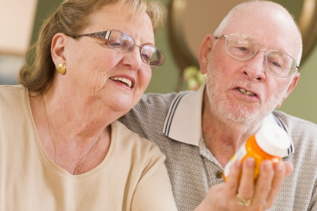 Curious Senior Couple Reading Prescription Medicine Bottle Together. photo