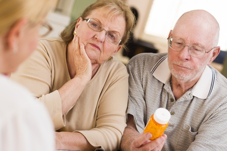 Doctor or Nurse Explaining Prescription Medicine to Attentive Senior Couple. photo