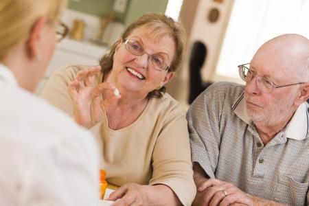 home health care: Doctor or Nurse Explaining Prescription Medicine to Attentive Senior Couple.