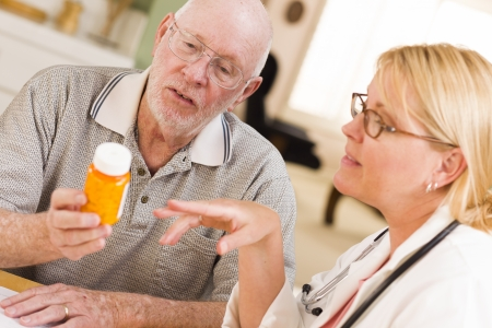 Doctor or Nurse Explaining Prescription Medicine to Attentive Senior Man. photo