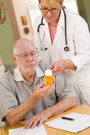 Doctor or Nurse Explaining Prescription Medicine to Attentive Senior Man. Stock Photo - 19126473