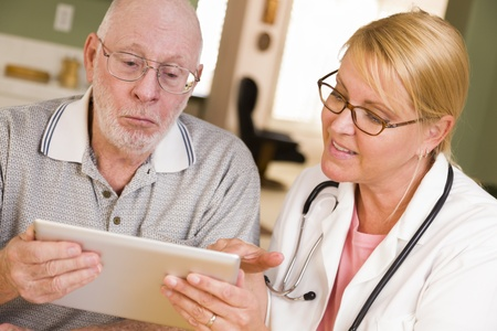 old home office: Doctor or Nurse Talking to Senior Man with Touch Pad Computer. Stock Photo