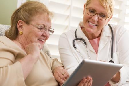 raton: Doctor o enfermera habla con la mujer mayor con el ordenador panel t�ctil. Foto de archivo