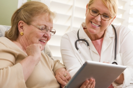 pad: Doctor or Nurse Talking to Senior Woman with Touch Pad Computer. Stock Photo