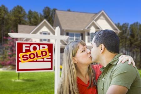 mixed race couple: Feliz pareja de raza mixta delante de Home vendido para venta inmobiliaria signo y casa
