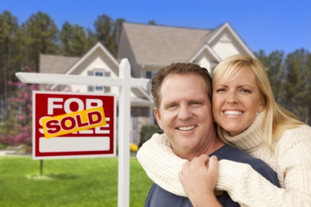 Happy Couple Hugging in Front of Sold Real Estate Sign and House