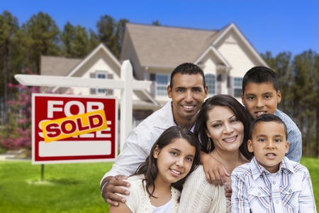 Happy Hispanic Family in Front of Their New House and Sold Home For Sale Real Estate Sign  photo