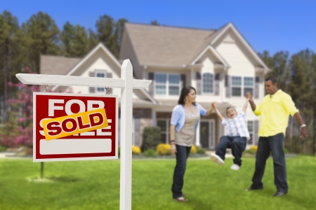 Happy Hispanic Family in Front of Their New House and Sold Home For Sale Real Estate Sign  Imagens