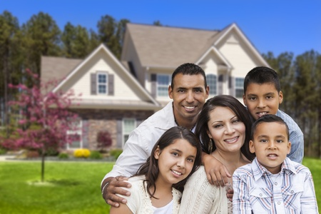 Happy Hispanic Family Portrait in Front of Beautiful House  Banque d'images