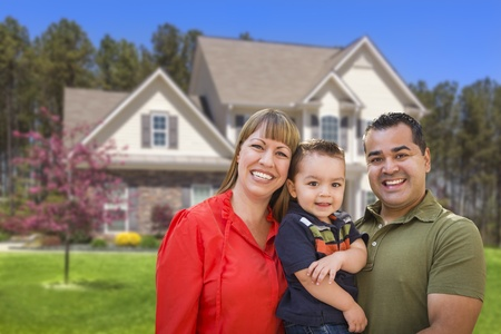 latino family: Happy Mixed Race Young Family in Front of Beautiful House