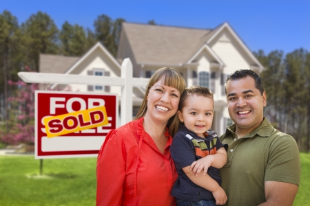real estate sold: Mixed Race Young Family in Front of Sold Home For Sale Real Estate Sign and New House