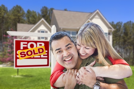 Happy Hugging Mixed Race Couple in Front of Sold Home For Sale Real Estate Sign and House  photo