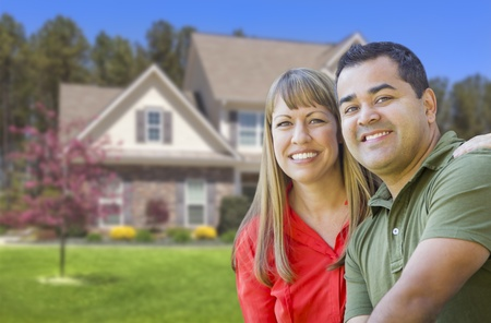 mixed race couple: Feliz pareja de raza mixta en frente de casa hermosa.