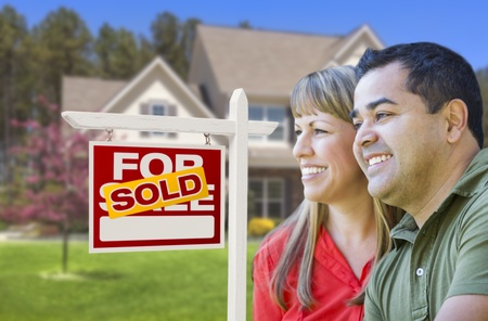 Happy Mixed Race Couple in Front of Sold Home For Sale Real Estate Sign and House. Stock Photo - 19196537