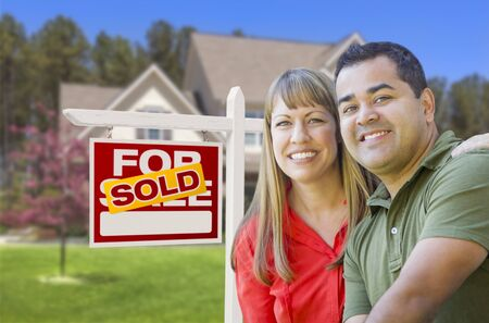 Happy Mixed Race Couple in Front of Sold Home For Sale Real Estate Sign and House. Stock Photo - 19196590