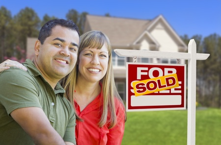 Happy Mixed Race Couple in Front of Sold Home For Sale Real Estate Sign and House. Stock Photo - 19196592