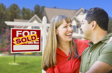 sell: Happy Mixed Race Couple in Front of Sold Home For Sale Real Estate Sign and House. Stock Photo