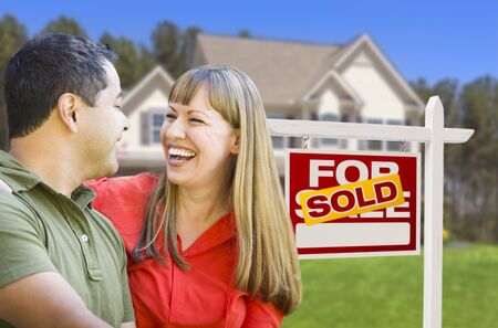 Happy Mixed Race Couple in Front of Sold Home For Sale Real Estate Sign and House. Stock Photo - 19196611