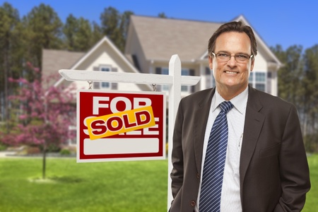 Male Real Estate Agent in Front of Sold Home For Sale Sign and House. photo