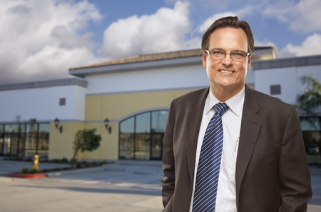 commercial real estate: Handsome Bussinesman In Front of Vacant Office Building.