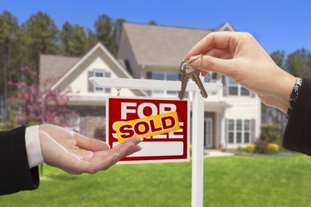 real estate: Real Estate Agent Handing Over the House Keys in Front of a Beautiful New Home.