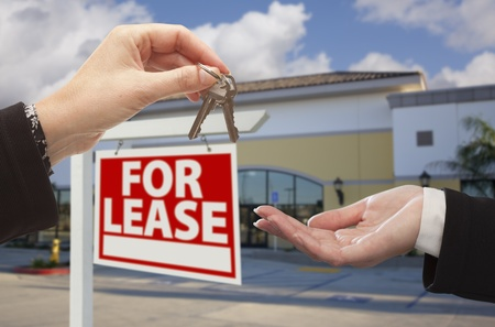 Real Estate Agent Handing Over the Keys in Front of Vacant Business Office and For Lease Sign. photo