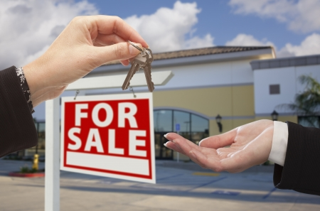 property for sale: Real Estate Agent Handing Over the Keys in Front of Vacant Business Office and For Sale Sign.