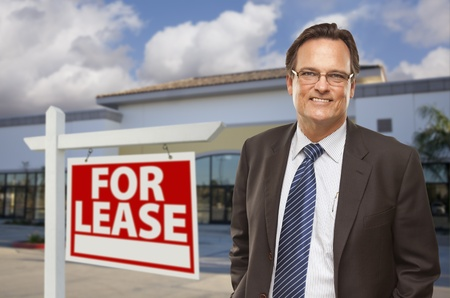 real: Handsome Businessman In Front of Vacant Office Building and For Lease Real Estate Sign.