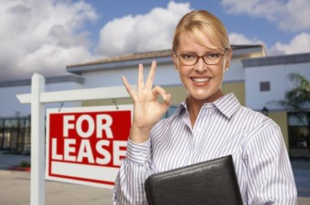 Lächelnde Geschäftsfrau mit OK Zeichen vor Vacant Bürogebäude und Vermietung von Immobilien anmelden.