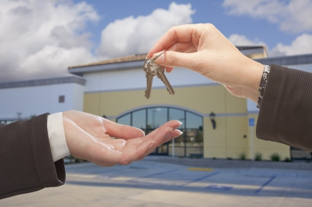 sell: Real Estate Agent Handing Over the Keys in Front of Vacant Business Office.