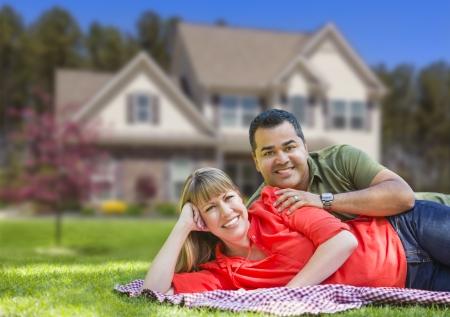 fachada de casa: Feliz pareja de raza mixta en frente de casa hermosa.