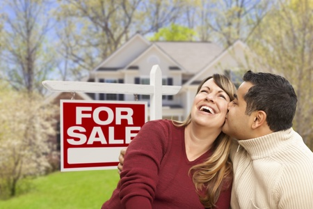 sell: Happy Couple in Front of For Sale Real Estate Sign and New House.