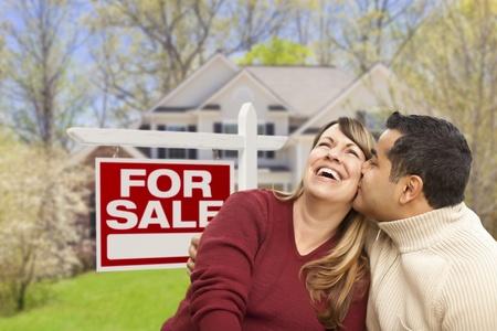 vendiendo: Pareja feliz delante de venta inmobiliaria signo y casa nueva. Foto de archivo