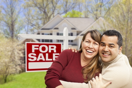 sales person: Happy Couple in Front of For Sale Real Estate Sign and New House.